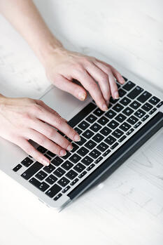 Womans hands typing on a laptop keyboard